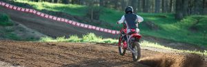 Rear of a person on a dirt bike riding on a track