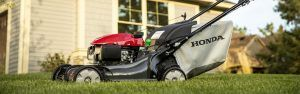 Side view of a Honda lawn mower in front of a house