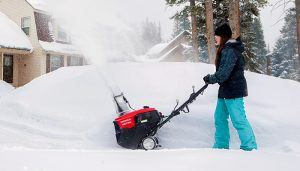 A woman using a single stage snowblower in front of a house by a mound of snow