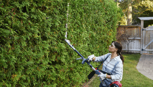 Woman using a VersAttach handheld on a hedge