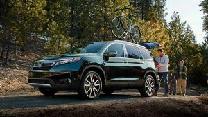 Side view of Honda Pilot with a bike on top and a man and son behind